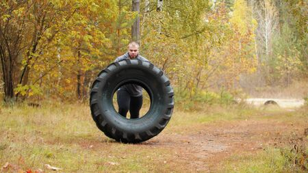 A big man bodybuilder turning over the tire on the ground and moving it forward - training outdoors in the autumn forest Stock fotó