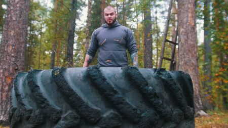 A big man bodybuilder standing near the tire. Stock fotó