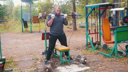 A man bodybuilder pulls up the dumbbells chained to the fitness equipment