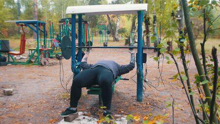 Ein Mann-Bodybuilder zieht die Hanteln hoch - Training auf dem Outdoor-Kindersportplatz