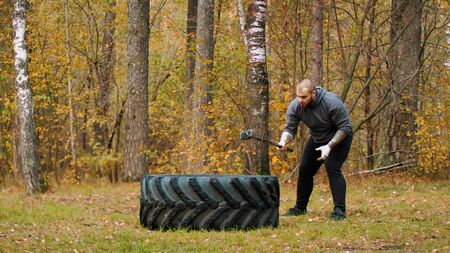 A tattooed man bodybuilder pushes over the tire on the ground - training outdoors. Stock fotó