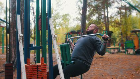 A man bodybuilder training on the outdoors sports ground