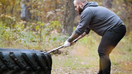 A big man bodybuilder hitting the truck tire - autumn forest