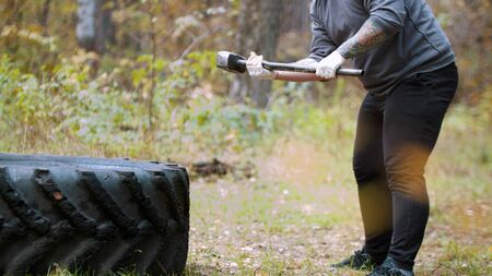 A big man bodybuilder hitting the truck tire with a hammer - autumn forest Stock fotó