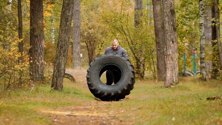 A big man bodybuilder turning over the tire on the floor and moving it - training outdoors