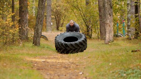 A big man bodybuilder turning over the tire on the ground and moving it - training outdoors in the autumn forest