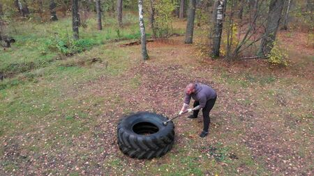 Tough man bodybuilder hitting the truck tire with a heavy iron hammer - tire hammering - training in the autumn forest