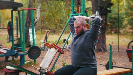 A man bodybuilder lowers the dumbbells behined - training on the outdoors kids sports ground Stock fotó