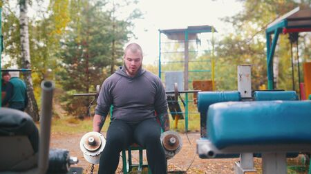 A man bodybuilder pulls up the dumbbells chained to the fitness equipment - training on the outdoors kids sports ground Stock fotó