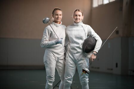 Two smiling women fencers at the school gym