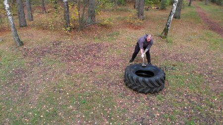 Tough tattooed man bodybuilder hitting the truck tire with a heavy iron hammer - training in the autumn forest Stock fotó