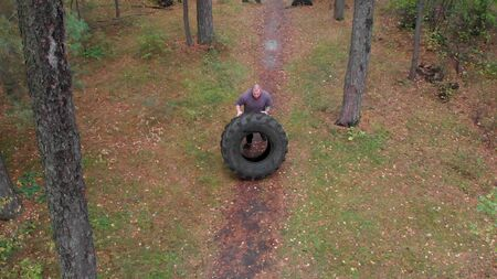 A tough man bodybuilder pushes over the tire on the ground in the forest