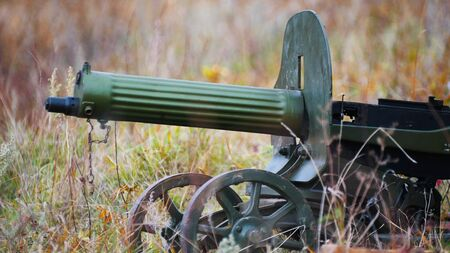 A green old machine gun standing on the field Stock fotó