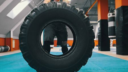 Tattooed powerlifter standing behind the huge tire