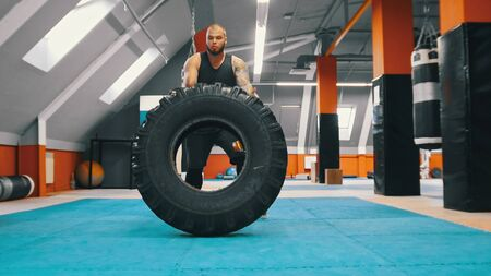 Big powerlifter standing with a huge tire