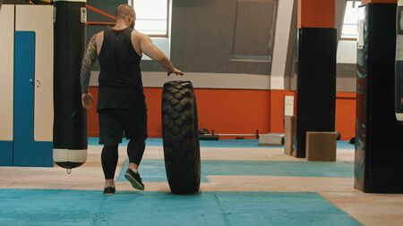 Athlete is rolling a huge tire to the wall
