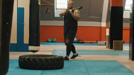 The powerlifter is standing by the tire with a big hammer on his shoulder