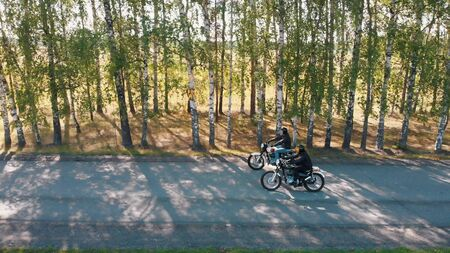 Two cool bikers are riding theis bikes on the road in the forest