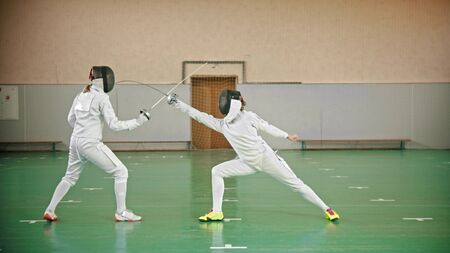 Two fencers are fighting in the school gym - indoor