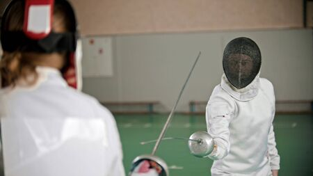 Fencers are attacking each other in the gym