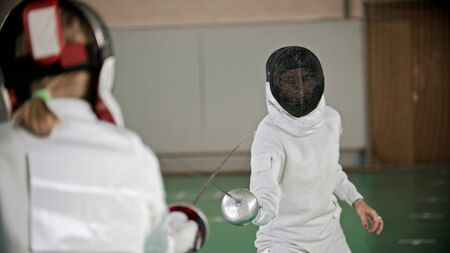 Young fencers are attacking each other in the school gym Banque d'images