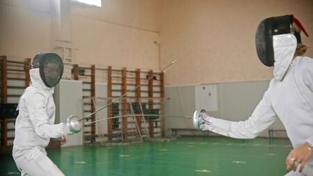 Two young fencers are matting in the school gym - indoor