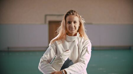 Young fencer is holding in hands a helmet and looking at the camera