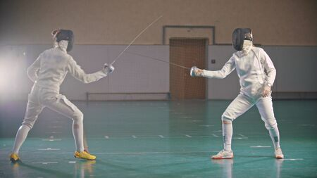 In the school gym wo fencers are training 写真素材