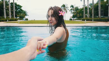 Young woman with flower is holding the hand of a guy in the swimming pool
