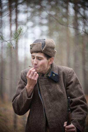 Un soldat de la Seconde Guerre mondiale tire sur un self-roll dans la forêt Banque d'images