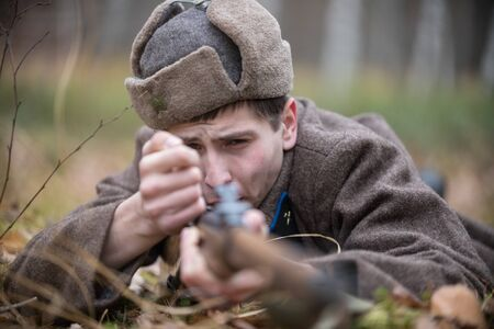 A soldier of World War II is reloading the rifle while lying on the battlefield