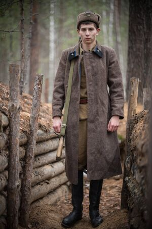 A young soldier of World War II is standing in the trench