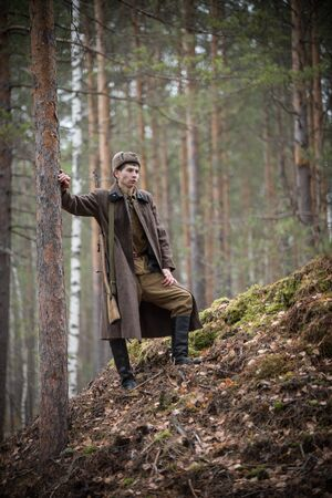A soldier of World War II is standing near the tree in the forest