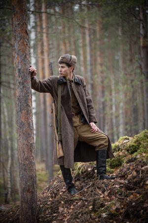 Un soldat de la Seconde Guerre mondiale se tient près de l'arbre et regarde à gauche Banque d'images