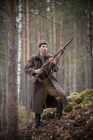A soldier of World War II is holding the rifle in his hands