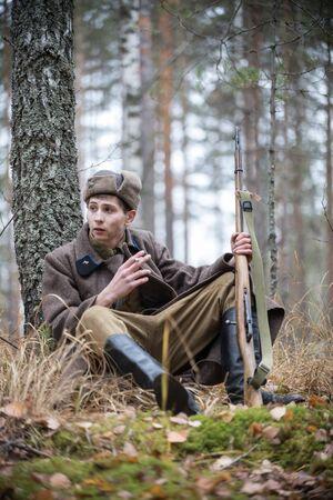 Un soldat de la Seconde Guerre mondiale avec un fusil est assis près de l'arbre et fume