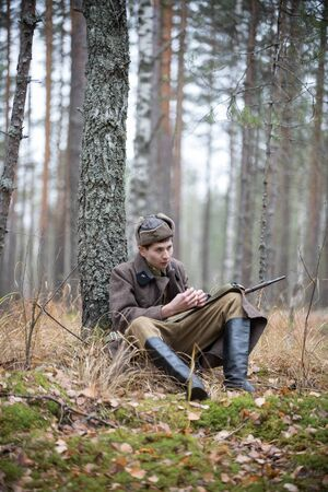 A soldier of World War II is sitting in the forest Banque d'images