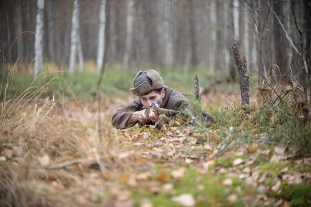 A soldier of World War II is lying in the forest and is going to shoot Stock Photo
