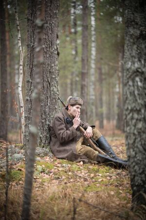 A soldier of World War II is sitting in the forest and smoking Banque d'images