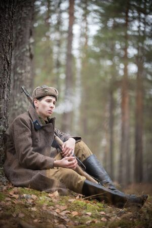 A soldier of World War II in military clothes is sitting in the forest and smoking