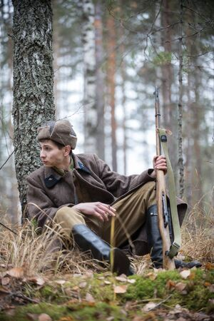 A soldier of World War II is sitting by the tree with a cigarette Banque d'images