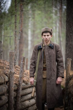 A soldier of World War II is standing in the trench