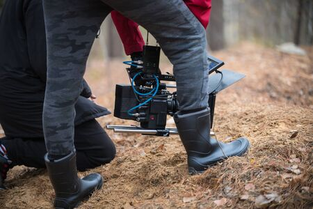 A man with camera in hand is filming in the forest