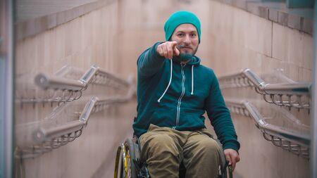 Behinderter Mann im Rollstuhl, der auf den Betrachter zeigt
