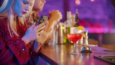 Young woman sitting by the bartender stand and using her phone - taking a photo of the drink