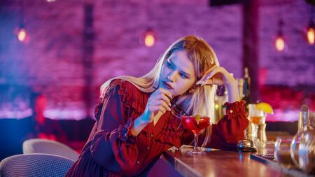 Gorgeous bored young woman sitting by the bartender stand and stirs the drink with a straw and looking to the side