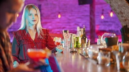 Gorgeous blonde young woman sitting by the bartender stand and looking in the camera - a man sitting in his phone on the foreground
