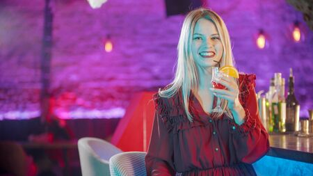 Gorgeous young woman sitting by the bartender stand and smiling with her teeth 写真素材