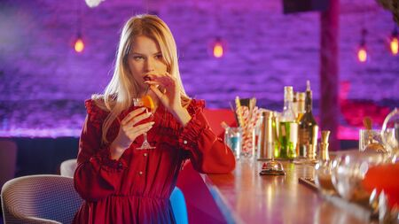 Gorgeous young woman sitting by the bartender stand - drinking a beverage from the straw