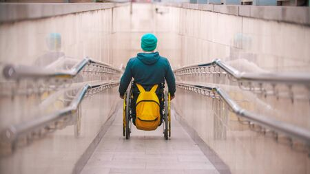 Disabled man in wheelchair going down the long ramp in the subway
